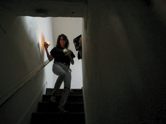 "Donna Golob carries lit sage, salt, a candle and holy water down the stairs as she performs a cleansing and blessing at a home York. Golob and other members of the Dover Paranormal Research Team will be featured on an upcoming episode of the Destination America show ""A Haunting."" The episode will focus on one of the team's investigations in Elkton, Md."
