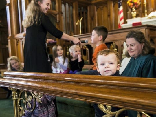 """Fifteen-month-old Antonio Disharoon, of Reisterstown, Md., pops his head over the railing in the Emmanuel United Church of Christ. Children were brought to the front of the congregation and sang """"Happy Birthday"""" to the church in honor of its 250 years of history."""