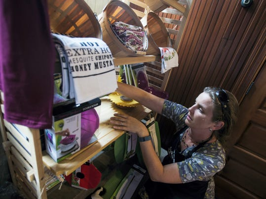 Heather Lunn, owner of the Carriage House Market, organizes a display shelf late last month in Hanover.  Lunn has owned the store behind the Sheppard Mansion for five years and focuses on selling local food and produce.