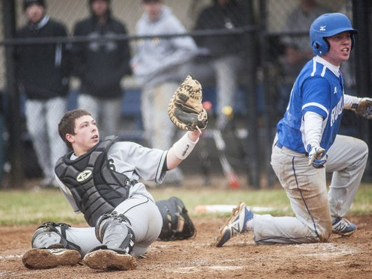 South Western catcher John Youngman and Spring Grove's Austin Piety look to the home plate umpire after a play at the plate.