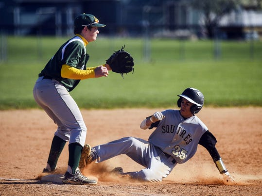 Delone Catholic's Evan Haymaker slides to third as York Catholic's Bryce Floyd looks for the ball during Friday's game at Delone Catholic. The Squires won, 11-1, to take control of first place in YAIAA Division IV.
