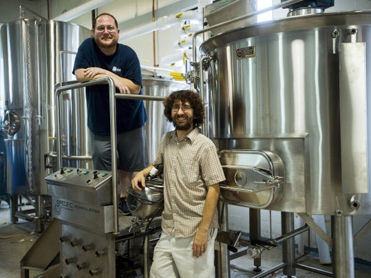 Aldus Brewing's President and CEO Jason Mininger, left, and Head Brewer Jeff Groves stand next to a mash tun, a machine that converts starch from barley into sugar, which is then used to make alcohol.