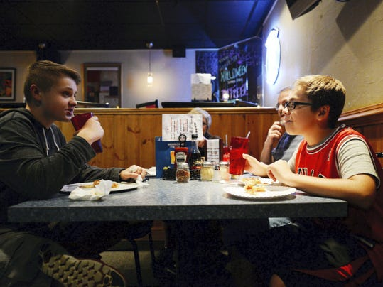 Cole Betterton, 13, left, and his friend Jimmy Dunn, 14, both of Mountville, eat pizza with Cole's parents Nancy Betterton, center, and Phillip Betterton, second from right, at Hurricane Pizza and Grill in Columbia.