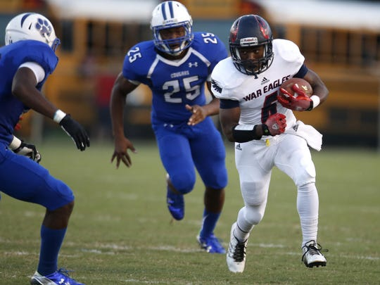 Wakulla's Cephus Greene runs in to Godby linebacker David Liburd during their game at Cox Stadium in the spring.