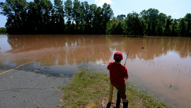 Calvin Carpenter goes fishing at Charles and Marie Hamel Memorial Park that is closed because of the high waters of the Red River.  The road that leads into the park is completely flooded.