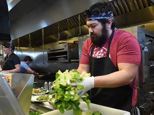 Kirk Provost moves lettuce to the prep table at Restaurant 415 on Friday, January 27, 2017.