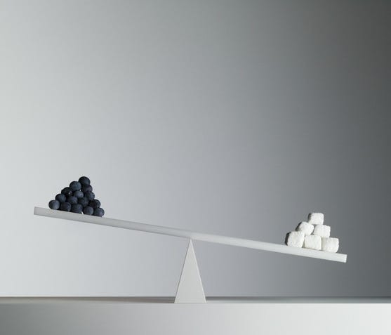 A seesaw with a pyramid of small black spheres on the left and larger white cubes on the right, against a blank gray wall.