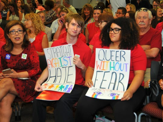Ryan Lyndermann and Veronica Hernandez hold signs during a Brevard County school board meeting, during which board members passed a non-discrimination policy that prohibits employment discrimination and student harassment based on gender identity or sexual orientation.