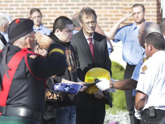 Town of Oneida Volunteer Fire Department Chief Chet Olson presents a helmet and flag to the family of firefighter John Brocker Nov. 7, 2016 in Seymour. More than 200 firefighters, police and personnel from about 50 Wisconsin agencies attended the service.