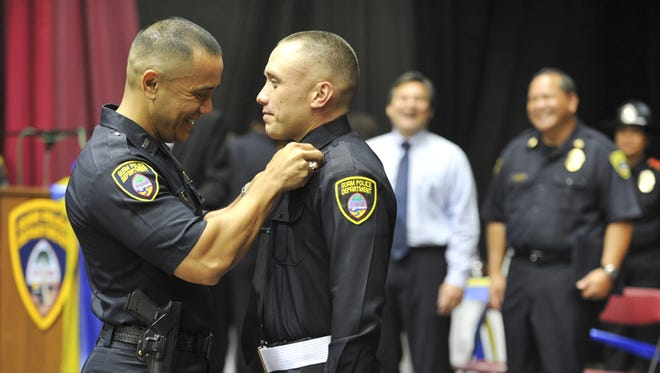 Father and son: Guam Police Department Lt. Mark Torre, left, pins a police badge on the uniform of his son, Mark Torre Jr., during the graduation ceremony for the fourth trainee cycle at the Father Duenas Memorial School gym on Aug. 4, 2011. The younger Torre graduated as the valedictorian of his class. Twelve graduates became police officers after completing 1,167 hours of training, which started in December 2010, according to a press release.