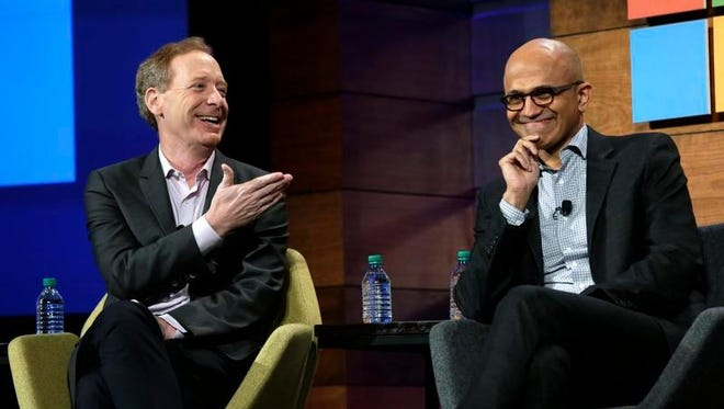Microsoft CEO Satya Nadella, right, looks on as Brad Smith, president and chief legal officer, smiles as he answers a question about New England Patriots head coach Bill Belichick's negative comments about the Microsoft Surface tablet device, at the annual Microsoft shareholders meeting, Wednesday in Bellevue, Wash. Nadella earned his master's degree at the University of Wisconsin-Milwaukee. Smith is a Wisconsin native who attended high school in Appleton.