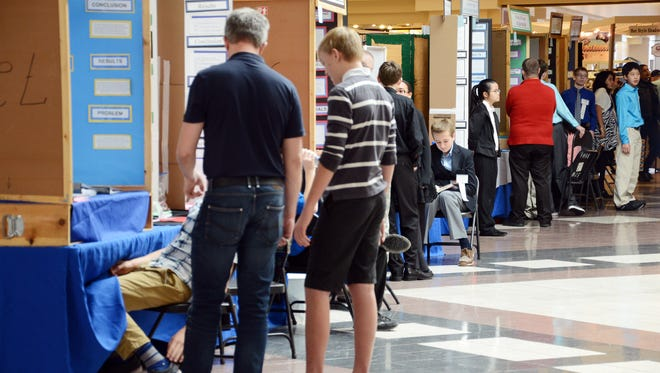 Students wait for judges to visit during the Brevard Intracoastal Regional Science and Engineering Fair at Merritt Square Mall last weekend.