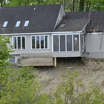 An embankment separating 292 Plattsburg Avenue and the Winooski River slid into the water on Sunday, leaving trees and sand above the water. This is the view of the house on Sunday a few hours after the landslide.