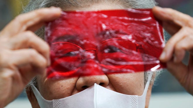 Kisako Motoki, 86, speaks, looking though a red cellophane depicting what she saw the atmosphere of the night of the Great Tokyo Air Raid on March 10, 1945, during an interview with the Associated Press at the Center for the Tokyo Raids and War Damage in Tokyo Wednesday, July 29, 2020. In Japan, war orphans were punished for surviving. They were bullied. They were called trash, sometimes rounded up by police and put in cages. Some were sent to institutions or sold for labor. They were targets of abuse and discrimination. Now, 75 years after the war's end, some are revealing their untold stories of recovery and pain, underscoring Japan's failure to help its own people.