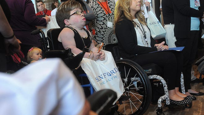 Kendra Gottsleben, Vicki Harkness and others listen during a news conference to publicly commemorate the 25th anniversary of the signing of the Americans with Disabilities Act at the Hilton Garden Inn Downtown Sioux Falls on Monday.