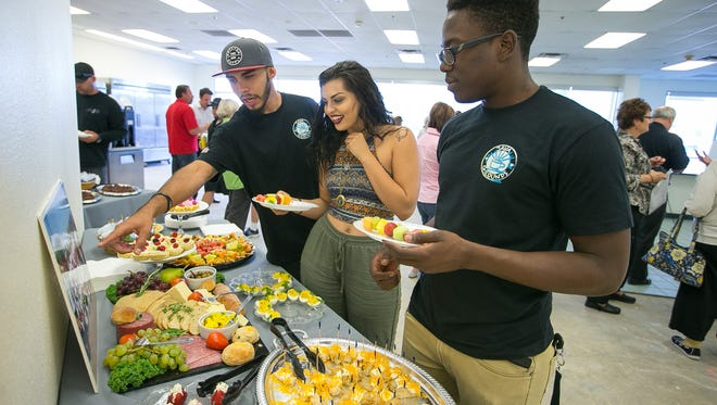 Employee David Lee, his friend Amber Torchia and employee Godfrey Mudavanhu try some of the hors d'oeuvres at the new Java Grounds location in downtown Peoria.
