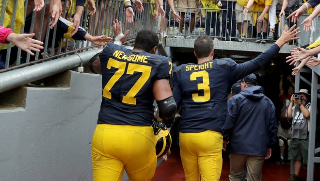 Michigan's Grant Newsome and Wilson Speight high-five the hands of Michigan fans as they head into the tunnel after their 51-14 defeat of UCF on Sept. 10, 2016.