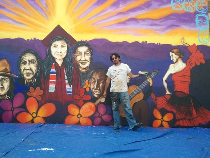 <p>Hugo Medina stands in front of a mural he painted with Thomas Breeze at ASU West for Hispanic Heritage month.</p>