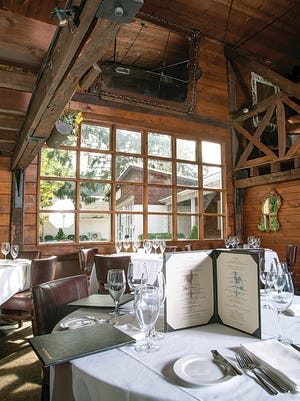 Bare windows allow sunlight to kiss the wood-paneled two-story dining room at the Saddle River Inn.