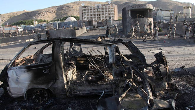 Afghan security personnel investigate the site of a suicide car bombing and a gunfight near the U.S. consulate in Herat Province, west of Kabul, Afghanistan on Sept. 13, 2013.