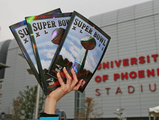 A man sells programs for $20 prior to Super Bowl XLII on Sunday, Feb 3, 2008 at the University of Phoenix Stadium in Glendale.