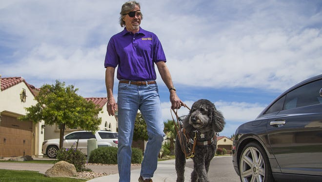 Steve Welker, who lost much of his vision in a car crash in 1994, walks with his seeing-eye dog, Orbit, near his home in Chandler on April 4, 2017.