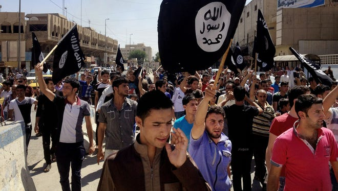 Demonstrators chant pro-Islamic State group slogans as they carry the group's flags in front of the provincial government headquarters in Mosul, Iraq, on June 16, 2014.