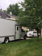A police evidence truck is parked in the driveway of