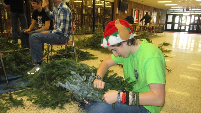 Kaulin Tomko makes a wreath to give to senior citizens on Community Service Day at SVE High School on Dec. 21.