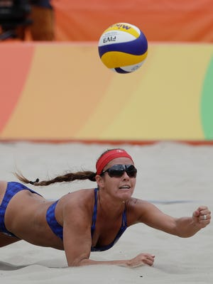 Unites States' Brooke Sweat dives for the ball against Poland during a women's beach volleyball match at the 2016 Summer Olympics in Rio de Janeiro, Brazil, Sunday, Aug. 7, 2016. (AP Photo/Marcio Jose Sanchez)