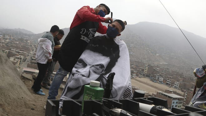 Barber Josue Yacahuanca styles the hair of a resident free of charge at the top of a hill in the San Juan de Lurigancho neighborhood of Lima, Peru, Friday.
