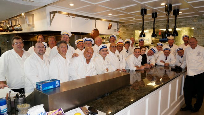Chef Anthony Bucco and sous chef Martyna Krowicka pose with the members of Les Marmitons at the kitchen of the Ryland Inn in November 2013