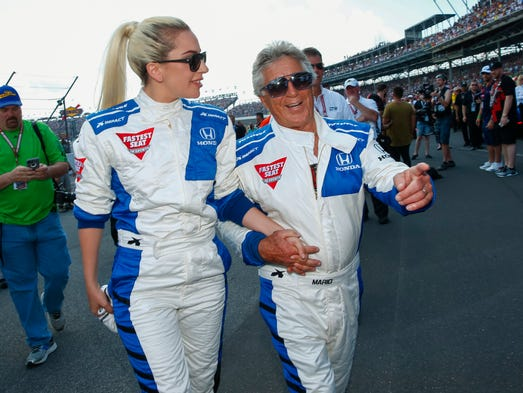 Lady Gaga and Mario Andretti walk to the track before