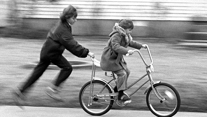 Almost as quickly as children find what Santa's left behind, they head outside to give the new toys a try. The cool, cloudy weather doesn't seem to matter as Vickie Turner, 11, helps her sister Rachael, 6, ride her new bicycle on Dec. 25, 1979. Vickie and Rachael are the daughters of Mr. and Mrs. William Turner of 991 Maria.