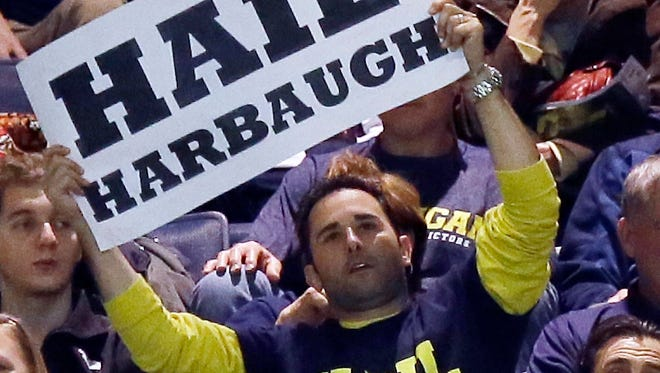 A Michigan fan at Crisler Arena holds up a sign for new football coach Jim Harbaugh in Ann Arbor on Dec. 30, 2014.