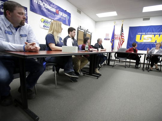 Sen. Tammy Baldwin, right, answers a question from Jessica Schiessl, a machine operator at Kimberly-Clark, second from left, while speaking with a group of K-C workers in Menasha.