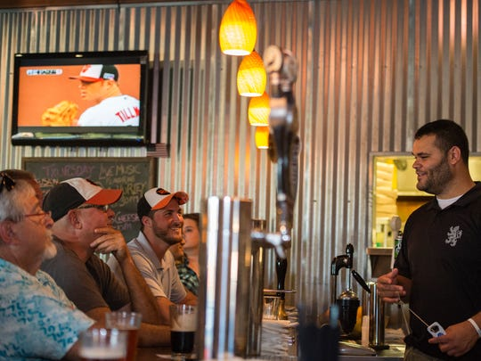 From left, Dudley Thompson of Girdle Tree, John Przylepa of Salisbury and Brian Koehler of Cambridge talk to bartender Donnie Jackson as they watch the Orioles face the Detroit Tigers in Game 1 of the AL Division Series at Specific Gravity in Salisbury.