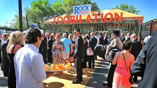 The crowd heads toward the main entrance to the 2014 Zoobilation party at the Indianapolis Zoo where this year's theme was Rock Your Orange. Over 5; 000 people attended the annual event sampling food from 70 restaurants.