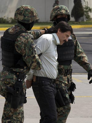 """Joaquin """"El Chapo"""" Guzman is escorted to a helicopter in handcuffs by Mexican navy marines at a navy hanger in Mexico City in 2014."""