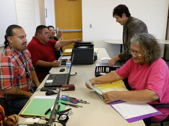 State of New Mexico officials and volunteers help Betty Largo, right, with her birth certificate paper work, Thursday, Sept. 22, 2016 at the Northern Navajo Agency Nataani Nez Complex in Shiprock.