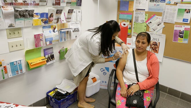 Walgreens pharmacist Jennifer de Jesus administers a free influenza vaccine to Ana Navarro, 33, during the Binational Health Week event at the Mexican Consulate in Los Angeles.