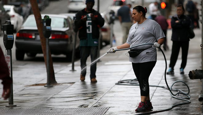 A woman uses a hose to wash the sidewalk in front of an apartment building on Tuesday in San Francisco.