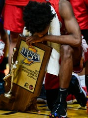 Bosse's Mekhi Lairy (2) holds onto the Class 3A Runner-Up trophy as he waits for a team picture at Bankers Life Fieldhouse in Indianapolis, Saturday, March 24. The Bulldogs were defeated by the Culver Academies Eagles, 64-49.