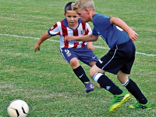 Eight-year-old Adrian Franco of Artesia's FC Athletico (5) and nine-year-old Guy Johnson (3) of Carlsbad's Titians FC go after the ball Saturday at Bob Forrest Youth Sports Complex.