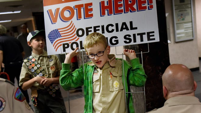 Parker Strain with the Boy Scouts of America Troop 48 carries a voting sign while helping out after the polls closed on Tuesday at the Minnehaha County Administration Building.