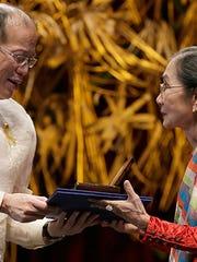 President Benigno Aquino III (left) presents the Ramon Magsaysay award to Ligaya Fernando-Amilbangsa of the Philippines in a ceremony Monday, August 31, 2015, at the Cultural Center of the Philippines in Manila.