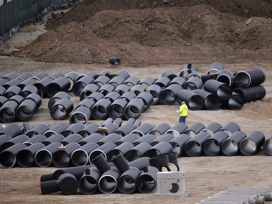 Stockpiles of pipe in a storage area at the Titletown District construction site looking west from Lambeau Field May 4,  2016.