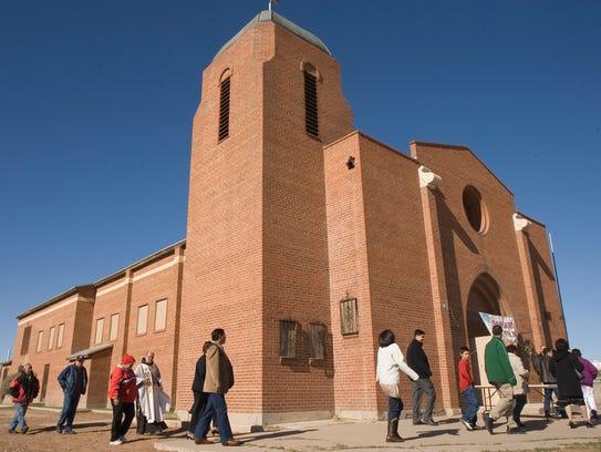 Father Luis Baldonado joins worshipers walking into