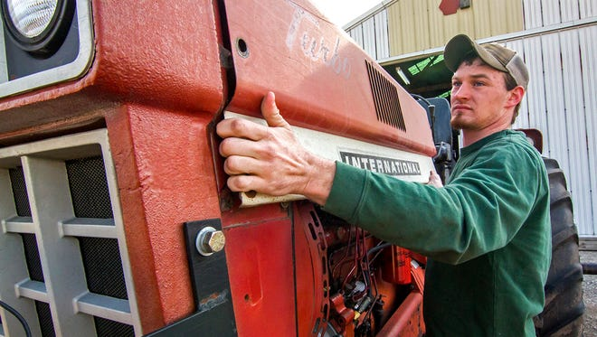 In this April 17, 2018 photo Theodore Kessler re-installs the hood on his family's 1466 International tractor after making several repairs on their farm in Strasburg, Ill. Theodore,  plans to finish his degrees in agricultural production and business at Lake Land College and then eventually farm full-time.