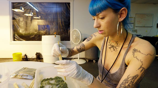 Stevie Askew, a worker at Sea of Green Farms in Seattle, packs recreational marijuana into blunts that will be sold in stores when legal recreational pot sales begin Tuesday in Washington state.